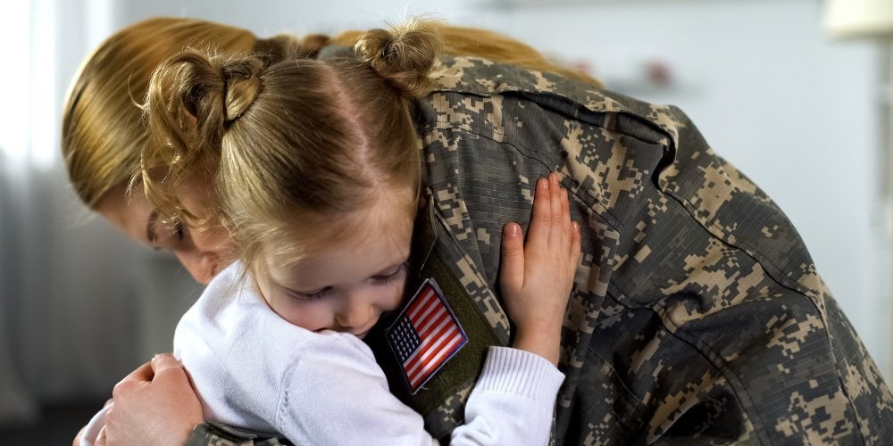 Mom soldier embracing little girl
