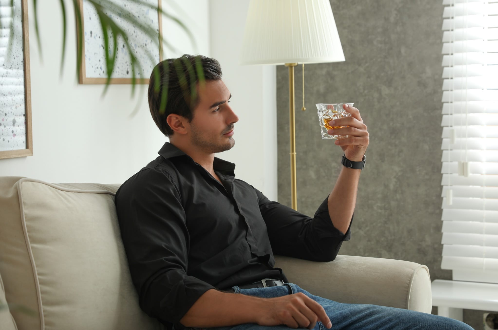 Young man with glass of whiskey at home (photo)