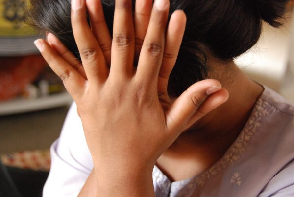Woman with hands in front of face